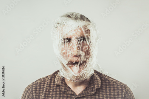 Photo Choking a Man Wrapped in Clingfilm