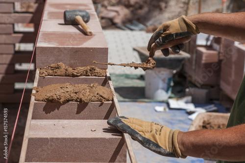 Foto op Plexiglas Wand maçon construisant un mur