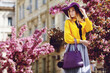 Outdoor portrait of young beautiful girl posing in street. Model wearing stylish hat, shirt, skirt, holding purple bag, handbag. City lifestyle. Female fashion concept. Copy, empty space for text