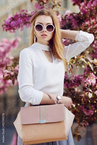 Plakat Plenerowa talia w górę portreta młoda piękna dziewczyna pozuje w ulicie. Model nosi stylowe okrągłe okulary, biała koszula, zegarek na rękę, trzyma różową torbę, torebkę. Styl życia w mieście. Kobiece pojęcie mody