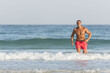 Mature older muscular fit Arab Male running out of the ocean on the beach, shirtless, wearing red shorts
