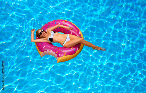 Woman in bikini on the inflatable mattress in the swimming pool.
