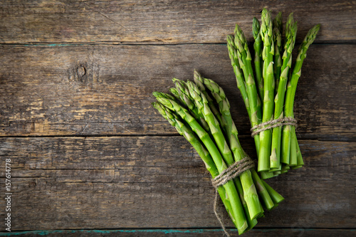 wooden bacckground with bunches of fresh green asparagus Wallpaper Mural