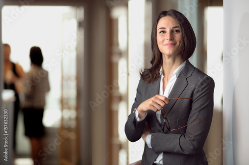 Obraz Candid portrait of a joyful cheerful happy employee staff member leader at the office workspace - fototapety do salonu