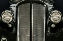 Front Headlights And Grille Of A Restored Vintage Car And Hood Ornament, Close Up Frontal. Vintage