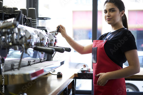 Poster Fitness Confident attractive female barista checking coffee machine before starting to work and opening cafeteria, portrait of charming waitress standing on workplace ready to make ordering enjoying her job