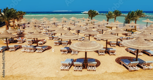 Tuinposter Egypte Chaise lounge and parasols on the beach against the blue sky and sea. Egypt, Hurghada
