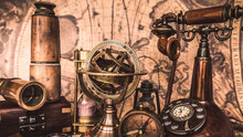 Antique Sundial Compass, Compass, Telescope, Vintage Telephone And Wooden Chest Box On Ancient World Map.
