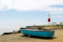 Wooden Boat By The Seaside And Portland Bill Lighthouse On The Isle Of Portland In Dorset, UK On The Background
