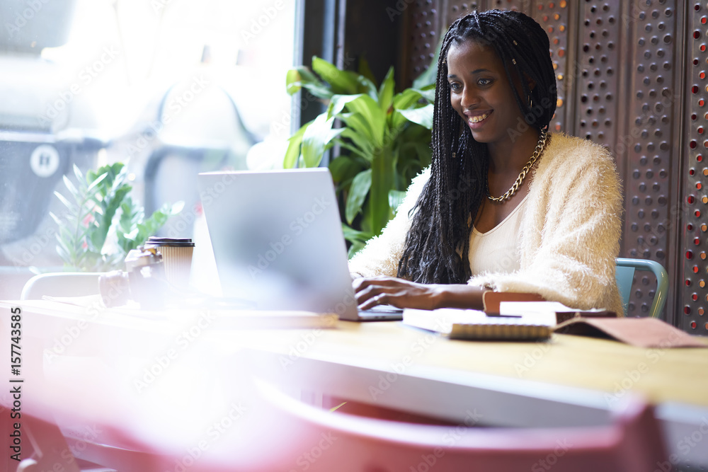 Fototapety, obrazy: Cheerful young afro American hipster girl having internet conversation through video chat with future classmates making friends and preparing for education abroad using laptop computer studying hard
