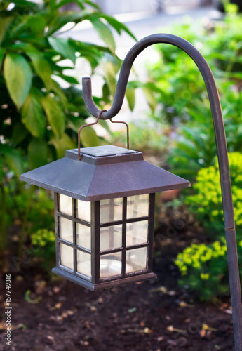 Photo  Garden lighting - lights on the solar battery on a green lawn