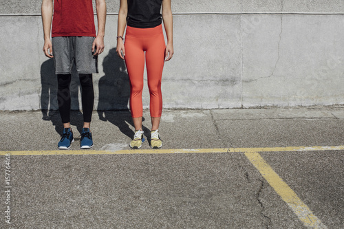 Cropped unrecognisable sportswoman and sportsman standing outdoors in sportswear.