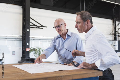 Two businessmen looking at plan on table in factory