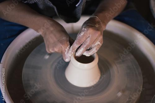 mains de céramiste sur le tourneau poterie