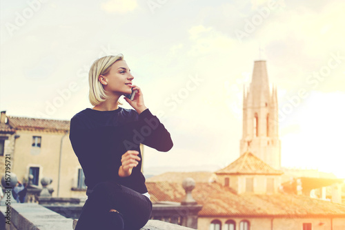 Foto  Young beautiful woman with good mood is talking on mobile phone, while is sitting on a building roof