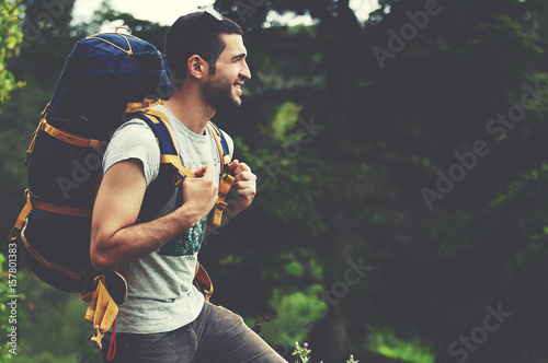 Fotografiet Portrait of young active traveler with a rucksack stands on a hilltop and enjoyi