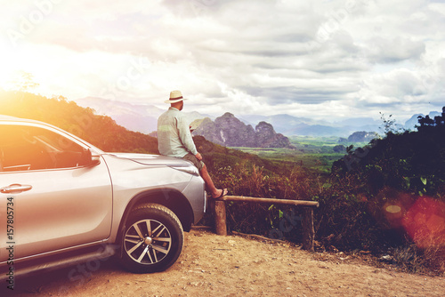 Fotografia  Dreaming man traveler is enjoying freedom and fantastic jungle view, while is sitting on a car hood in summer evening