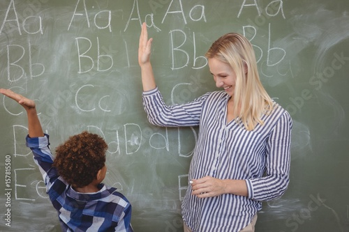 Foto  Happy teacher and schoolboy giving high five in classroom