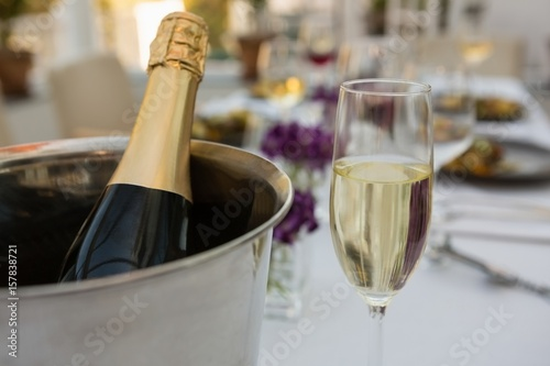 Champagne bottle in bucket with glass on table in restaurant