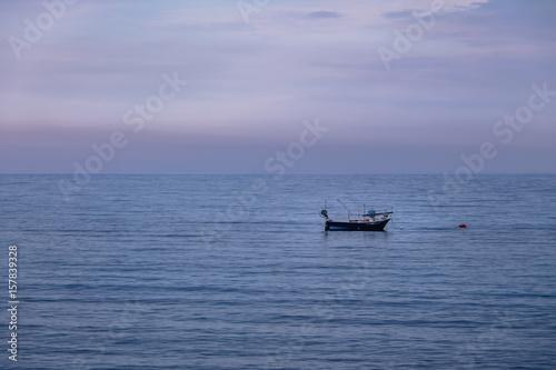 Fotografie, Obraz  A boat in a Mediterranean beach of Ionian Sea at sunset - Bova Marina, Calabria,