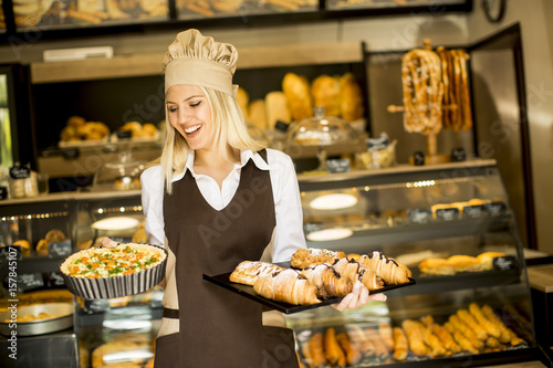 In de dag Bakkerij Young female baker standing in the bakery, shows pizza and croissants