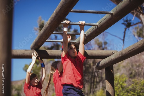 Kids climbing monkey bars during obstacle course training