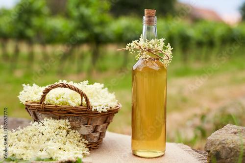 Homemade elderflower syrup in a bottle and basket with elderflowers