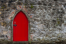 Red Painted Wooden Door On Old Stone Wall Church Building