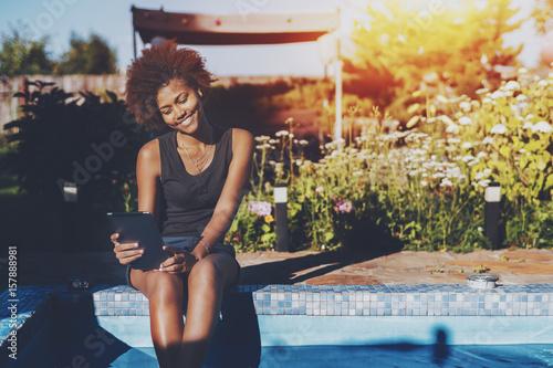 Valokuva  Cheerful lovely young black girl enjoying her leisure time sitting near swimming