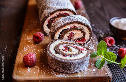 Fototapeta Chocolate roll cake with coconut and raspberry filling