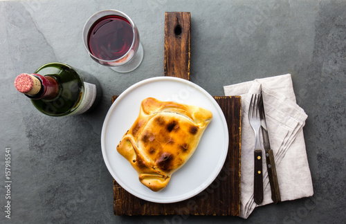 Chilean baked empanada de pino with meat, olives, onion and eggs served on wite plate with wine