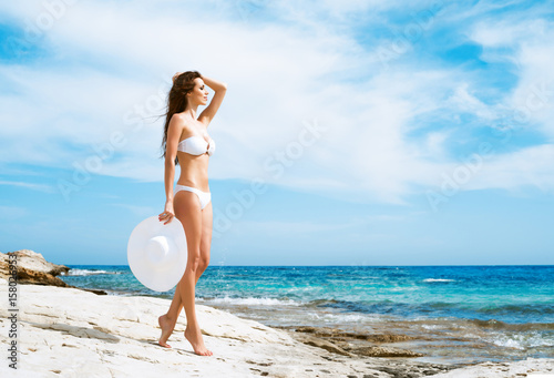 a2980d86ac Beautiful woman in white bikini. Young and sporty girl posing on a beach at  summer.