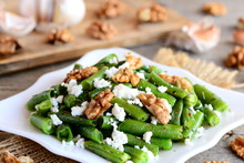 Vinegar And Oil Green Bean Salad Recipe. Delicious Green String Beans Salad With Cottage Cheese, Peeled Walnuts, Garlic And Spices On A White Plate And Wooden Table. Warm Salad For Healthy Dinner Idea