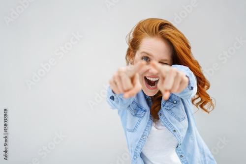 Fotografija  lachende frau zeigt nach vorn