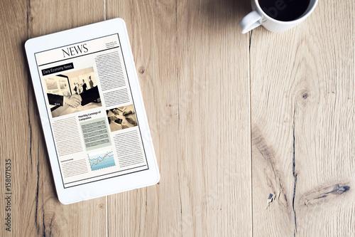 Newspaper on digital tablet on wooden table