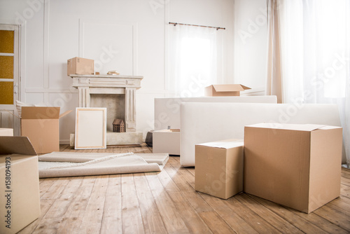 Fototapeta Picture frame and cardboard boxes in empty room, relocation concept obraz