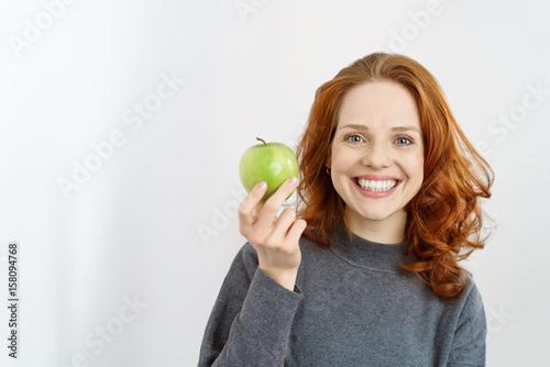 frau zeigt einen leckeren grünen apfel Wallpaper Mural