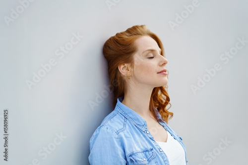 Fototapeta entspannte frau lehnt mit geschlossenen augen an einer wand obraz