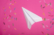 Top view of white paper plane and colorful paper clips isolated on pink