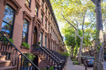 Scenic View Of A Classic Brooklyn Brownstone Block With A Long Facade And Ornate Stoop Balustrades On A Summer Day In New York City
