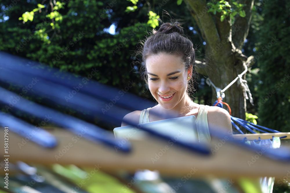 Fototapeta Czytanie książki. Młoda kobieta wypoczywa na hamaku