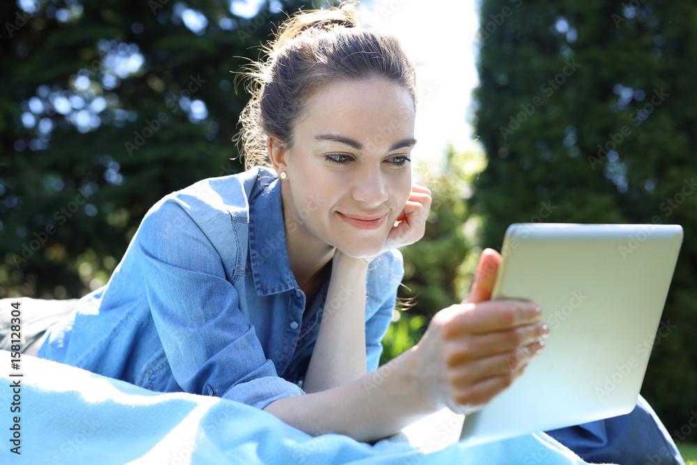 Fototapeta Wakacyjne lenistwo na łonie natury. Piękna, młoda kobieta wypoczywa czytając tablet siedząc na kocu