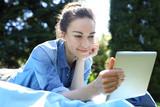 Wakacyjne lenistwo na łonie natury. Piękna, młoda kobieta wypoczywa czytając tablet siedząc na kocu