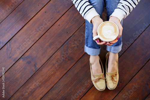 Woman holding in hands cup of coffee with milk sitting on the floor Wallpaper Mural