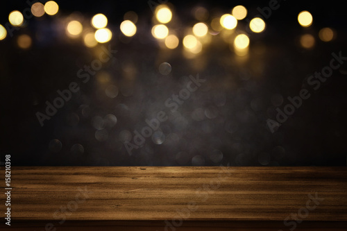 Tableau sur Toile Empty table in front of black and gold glitter lights background