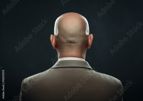 Fototapeta The back of a bald man in suit