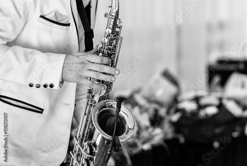 Zdjęcie XXL Saksofonista w białej kurtce gra na saksofonie. Saksofonisty jazzowy mężczyzna z saksofonem na przyjęciu weselnym