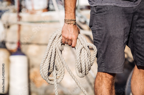 Closeup up of Yachtsman hands with yacht ropes