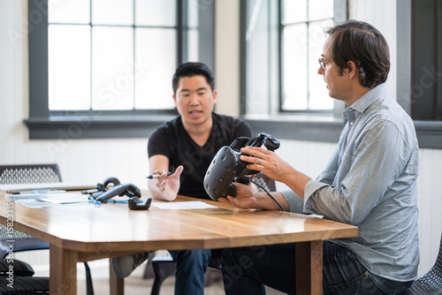 Photo  Business colleagues discuss while using a virtual reality headset