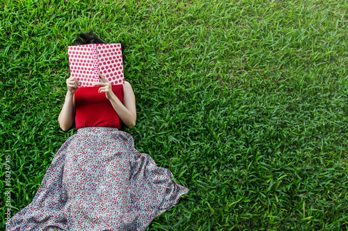 Fotografía  Woman lay down or relaxing on green grass reading book in summer or spring, top